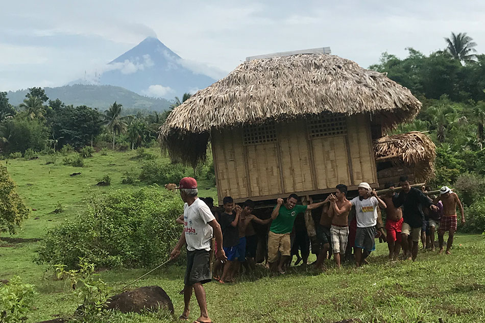 Local community carrying a small house to a safe location